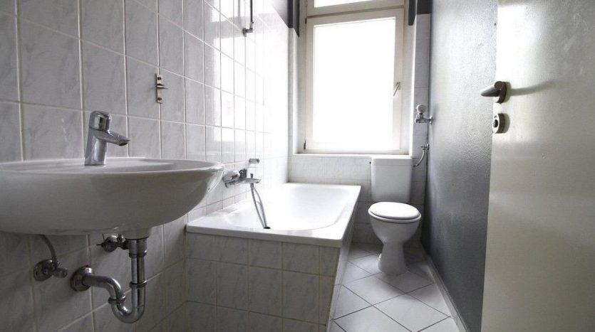 Salle de bain carrelée avec des toilettes et une grande fenêtre